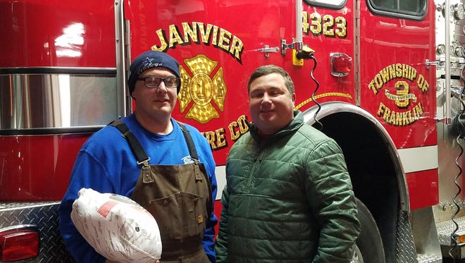 Janvier Volunteer Firefighter Mike Keenan (left) accepts a turkey from Sahara Sand Mine Manager Bill Fishburn.
