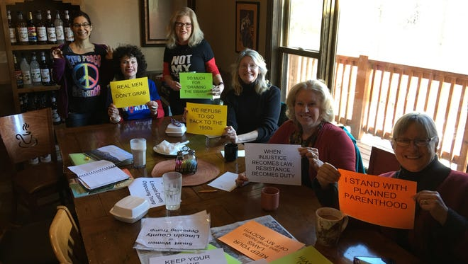 Local women who marked to protest parts of the Trump administration agenda display signs they carried in last Saturday's Women's Marches.