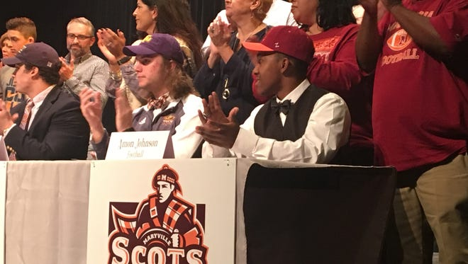 Farragut High School football players Amon Johnson, right, and Davis Simmons, left, celebrate signing with Maryville College and Tennessee Tech, respectively, on Wednesday, Feb. 1, 2017.