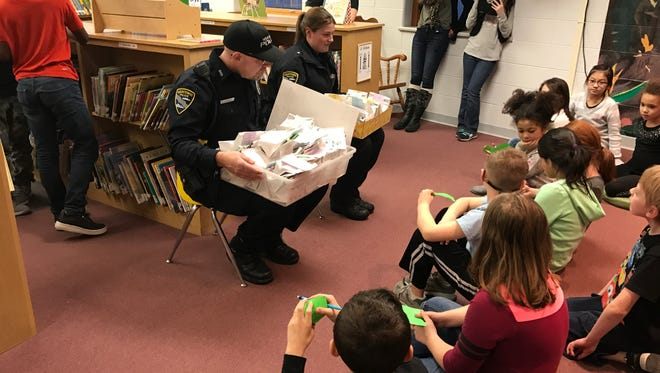Two Manitowoc police officers meet with Kindness Rocks students at Jefferson Elementary School Jan. 30 to accept treat bags the students prepared for all 64 officers and detectives on the force.