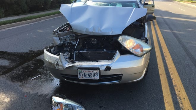 In this photo taken July 14, 2016, a car involved in an accident sits in the road McLean, Va. The Consumer Federation of America says it found premium hikes in some cases reaching $400. It looked at premium quotes in 10 cities from five of the nation's largest auto insurers and found that Progressive aggressively used a not-at-fault penalty, surcharging drivers in eight of the ten cities.
