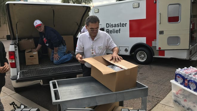 Dave Boyd, left, and Mike Vaughn, right, load up a truck with Red Cross materials to take to California.