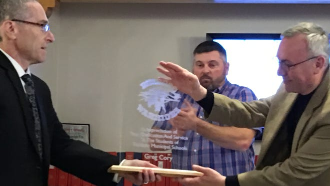 Departing school board president Greg Cory, right, accepts a plaque from school Supt. George Bickert in appreciation for his service.