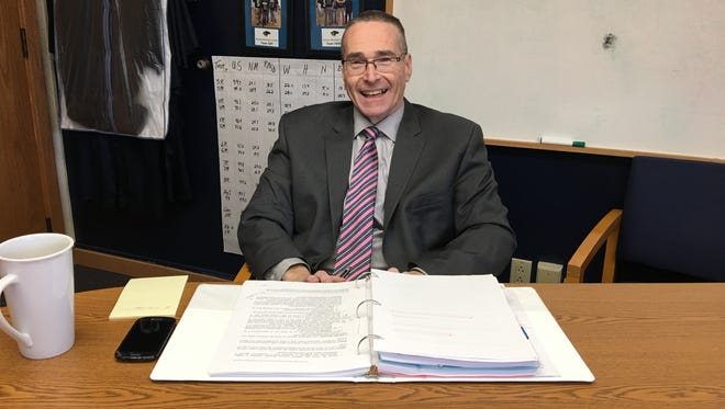 School Supt. George Bickert takes a break from examination of a thick binder containing details of Ruidoso's successful application for a School Impovement Grant.