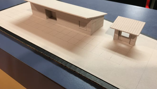 An architect's model shows plans for permanent rest rooms and a ticket kiosk for the middle school football field.