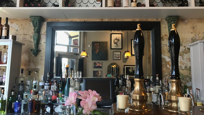 A self-portrait of Robert Busby is reflected Feb. 23, 2017 in the mirror of the bar at The Creole in Old Town. Busby, widely credited with the success of Old Town, died Feb. 27, 2007.