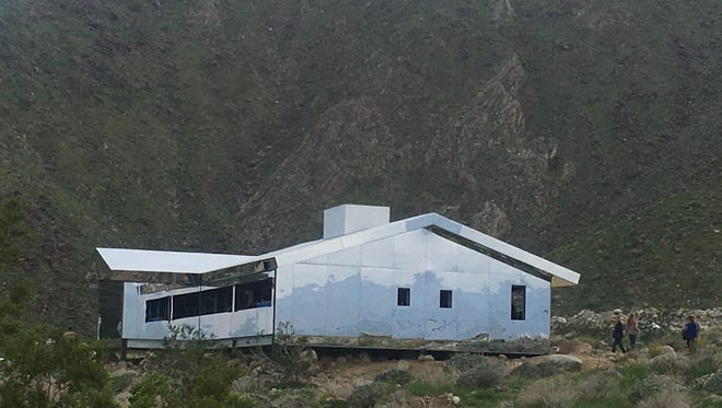 "Visitors head to ""Mirage,"" by artist Doug Aitken on Saturday, the first day of Desert X. The piece is a ranch-style home made entirely of mirrors. Aitken says the piece ""distills the recognizable and repetitious suburban home into the essence of its lines, reflecting and disappearing into the vast western landscape."""