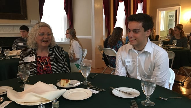Molly Brown (left), an associate dean at James Madison University's College of Business, shares a story with George Theiss, an 11th-grader at Riverheads High School, during lunch Saturday at the Woodrow Wilson Presidential Library & Museum.