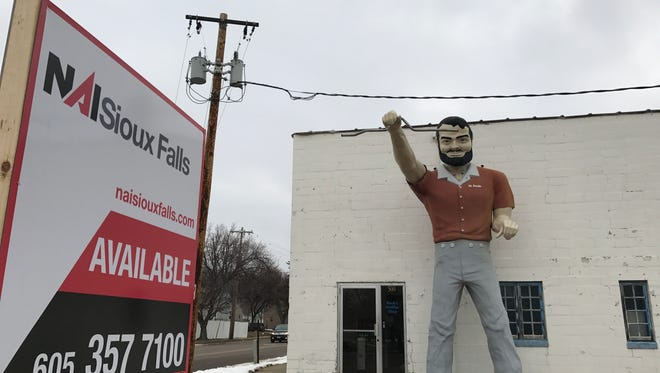 Buck's Muffler Shop is on the market, and the Mr. Bendo statue is part of the deal.