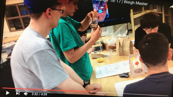 Concord High School students work to develop the Weigh Master, which helps workers with disabilities package dog treats.