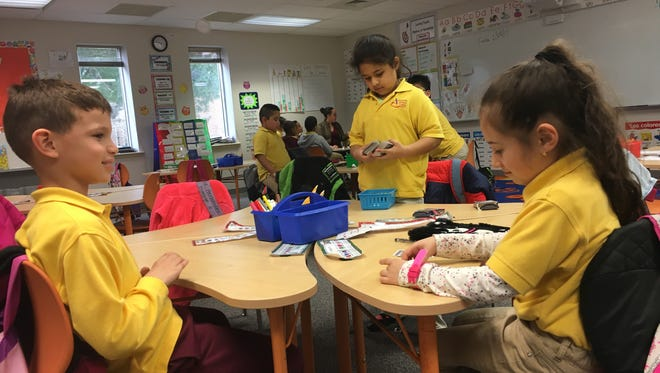 From left to right, Cole Granda, Dianice Hernandez and Jasnae DaValos, first-graders at Academia Antonia Alonso, work together in their first-floor classroom.