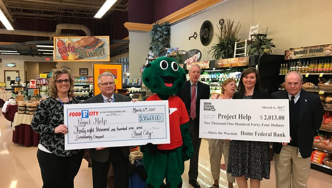 Representatives from Food City and Home Federal Bank present checks to Project Help. Food City raised $38,601 and Home Federal Bank raised $2,013. Pictured from left to right are Betsi James and Mickey Blazer of Food City, WVIK the Frog, Bill Evans and Jeanie Fox of Project Help, Amy Williams of Home Federal Bank and Dale Grubbs of KUB.
