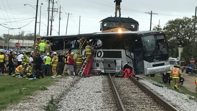 Biloxi firefighters assist injured passengers after their charter bus collided with a train in Biloxi, Miss., Tuesday, March 7, 2017.  Biloxi city spokesman Vincent Creel says emergency responders were still removing injured people from the bus more than 30 minutes after the crash. (John Fitzhugh/Sun Herald via AP)