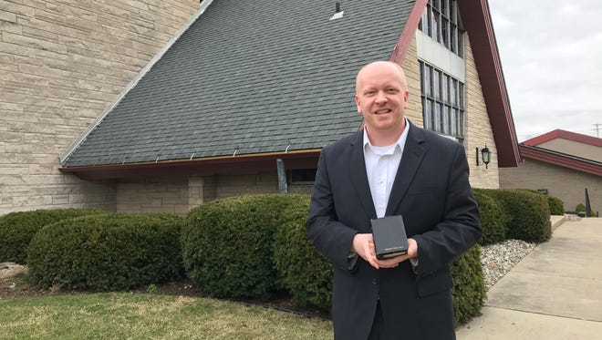 """Pastor Wes Peppers of the Lansing Seventh-day Adventist Church was a friend of the late Desmond T. Doss, a WWII medic whose story is featured in """"Hacksaw Ridge."""" Peppers holds Doss' Bible  outside his church March 6, 2017."""