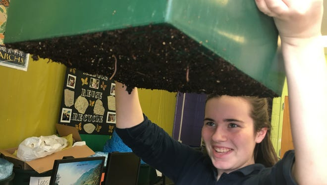 Katie Givens, an eighth-grader at Kirk Middle School, shows off a worm farm. It is part of a composting project the school's 4-H Recycling Club works on after school.