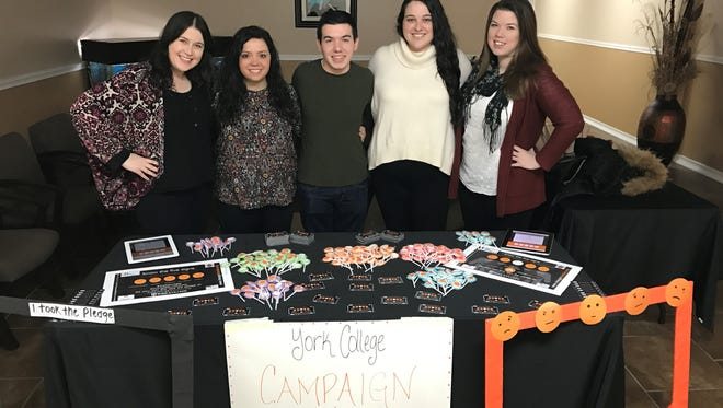 York College students, from left, Heidi Lineweaver, Carissa McQuade, Alexander Iula, Haley Keller and Lauren Milliken pose behind a table of materials for their mental health campaign at the Door of Salvation Church on Sunday, March 12, 2017.