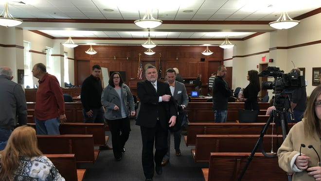 Former Boone County Sheriff's Detective Bruce McVay, center, leaves the courtroom Thursday after testifying. The hearing was to determine whether David Dooley will get retried in the murder of Michelle Mockbee.