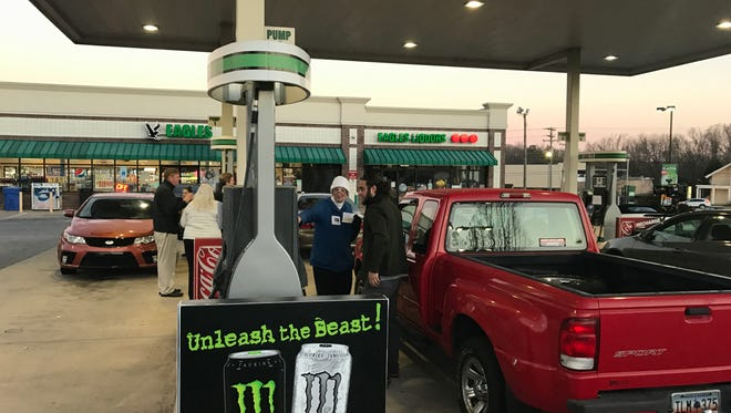 A member of FANofSC talks with a commuter about the gas tax. The group paid the gas tax for the first 1,000 gallons of gas sold at Eagles on Pelham Road on Monday, March 20, 2017.