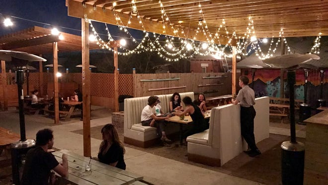 The large outdoor patio at Love Buzz, in the Five Points district, features booths, benches and a taco trailer, Valentine's Kitchen.