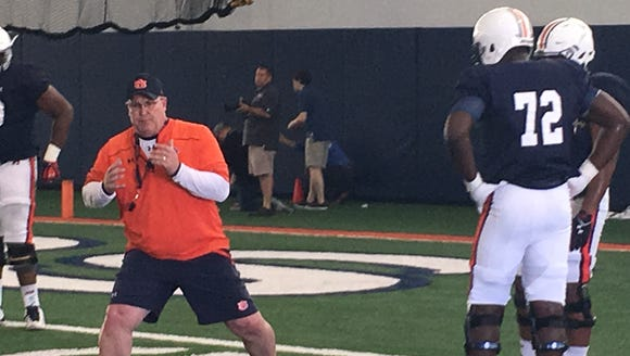 Auburn OL coach Herb Hand going over technique during