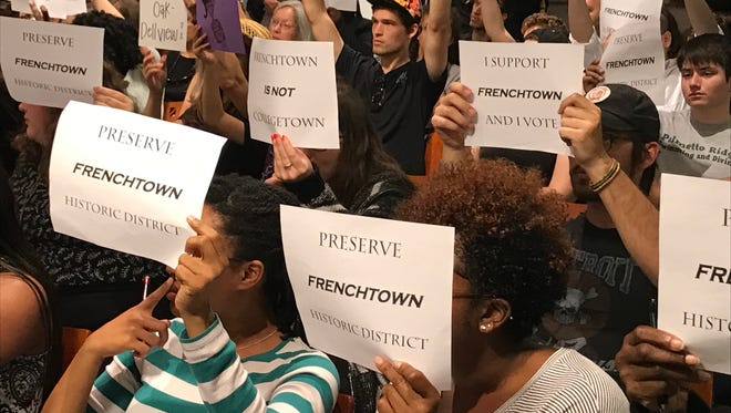 Residents hold up signs urging city commissioners to save Frenchtown.