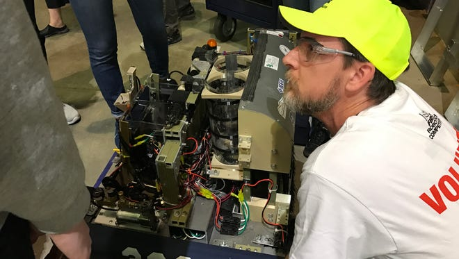Tim Klein, a volunteer inspector for the FIRST robotics competition, examines Hardin Valley Academy RoHAWKtics' robot before their practice match. Hardin Valley Academy, backed by ORNL, has won the Smoky Mountain Regional   before and competed in national championships.