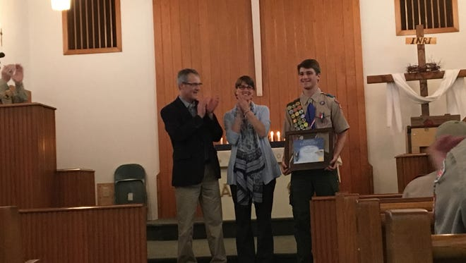 Luke Coffman, right, receives his Eagle Scout certificate Saturday at Northside United Methodist Church in Jackson.