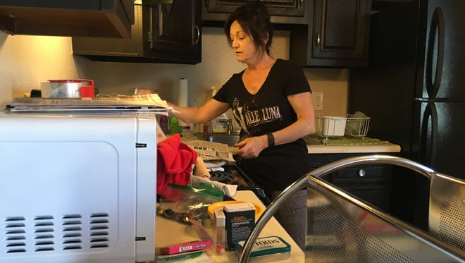Katrina Taylor packs her kitchen items, wrapping them in newspaper before stuffing them in boxes bound for storage. She wanted to keep most household items in storage, in hopes she'd be back into her own apartment by the summer.