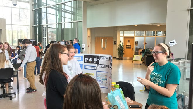 A member of the Purdue ASL club talks with attendees about ASL opportunities offered at Purdue University.