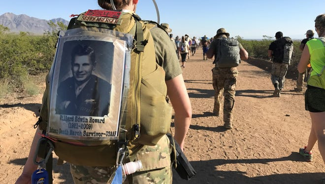 For Air Force 2nd Lt. Amber Schoenberger marches in the Bataan Memorial Death March Marathon March 19 at White Sands Missile Range, NM, in honor of her grandfather (pictured on her backpack), U.S. Army Air Forces Cpl Willard Edwin Howard (1921-2009), who survived the grueling march in 1942.