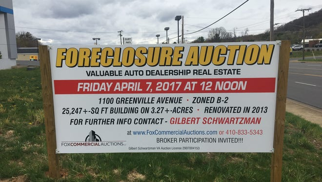 A sign outside the old Elliott Chevrolet and Cadillac on Greenville Avenue advertises an auction scheduled for Friday, April 7, at noon. The auction was canceled.