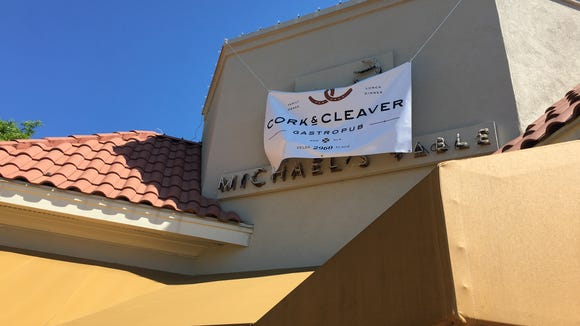 A temporary Cork & Cleaver banner hangs over the Michael's Table sign at the new gastropub.