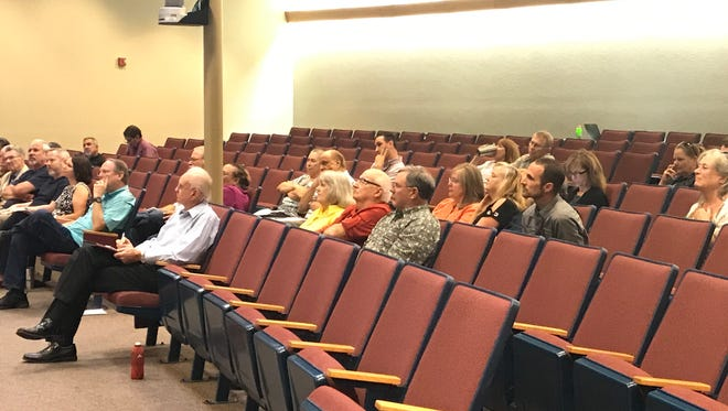 Pace resident Phil DeProtine, left, listens on Thursday, April 13, 2017, during a Santa Rosa Board of County Commissioners meeting on the closure of an entrance to the Cross Roads subdivision.