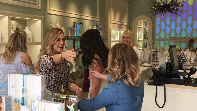 Kenosha native Kendra Scott (center) hugs employees Friday during a visit to Wisconsin's first Kendra Scott jewelry store, which opened last week at The Corners of Brookfield.