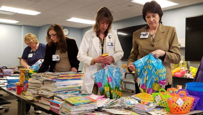 In the foreground, Sandra Neu, LPN, in the medical-surgical unit at Beaumont Hospital, Wayne, and Sandy Wright, manager of Respiratory Therapy at Beaumont Hospital, Wayne, put together Easter gift bags to be distributed to students in the community.