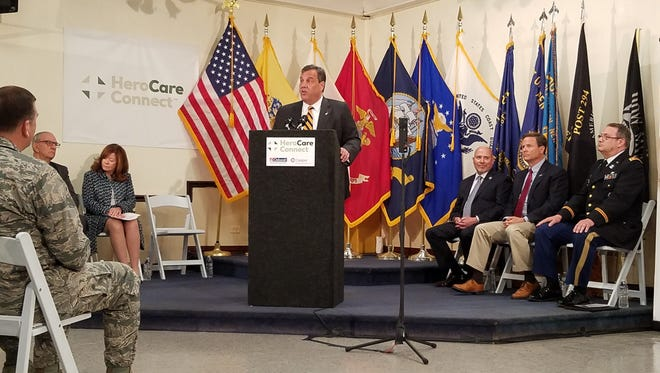 Gov. Chris Christie speaks at an event to celebrate the launch of HeroCare Connect at an American Legion Hall in Burlington County on Tuesday. Seated, third from right, is Republican Rep. Tom MacArthur of Toms River and second from right, Democratic Rep. Donald Norcross of Camden.