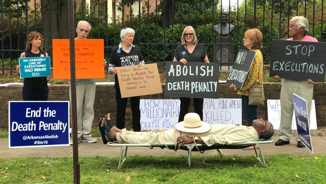 This photo provided by Sherry Simon shows Pulaski County Circuit Judge Wendell Griffen taking part of an anti-death penalty demonstration outside the Governor's Mansion Friday, April 14, 2017 in Little Rock, Ark.  Griffen issued a temporary restraining order Friday blocking the state from using its supply of vecuronium bromide after a company said it had sold the drug to the state for medical purposes, not capital punishment.   Local media outlets had tweeted photos and video of Griffen appearing to mimic an inmate strapped to a gurney at the demonstration.   Attorney General Leslie Rutledge's office said she planned to file an emergency request with the state Supreme Court to vacate Griffen's order, saying Griffen shouldn't handle the case.