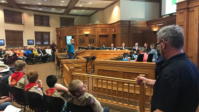 Troy Hokeness, a southwest Sioux Falls homeowner involved in the protest of a 85th Street and Brett Avenue rezone, talks at the podium inside Carnegie Town Hall Tuesday night as his colleagues stretch out a tape measure to illustrate how close a planned apartment would be to neighboring homes.