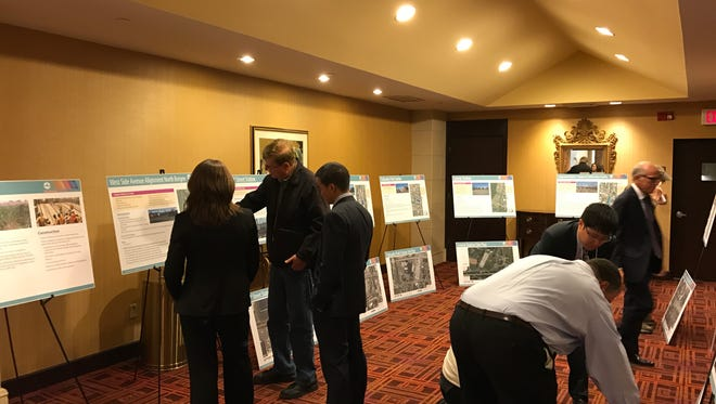 Residents look over information about the Hudson-Bergen Light Rail expansion at a public hearing on April 24. Representatives of NJ Transit were on hand to answer questions about the project.
