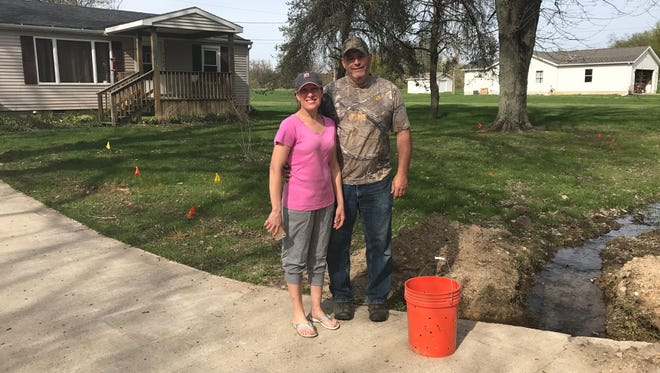 Michelle and Dell Graham, standing by the ditch April 24, 2017, say their basement is being flooded by their neighbor.