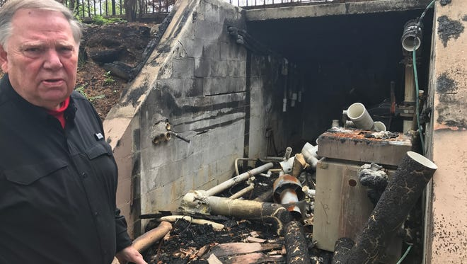 Stan Johnson, treasurer of Chalet Village Owners Club, stands by the burnt-out pool house at the north clubhouse.