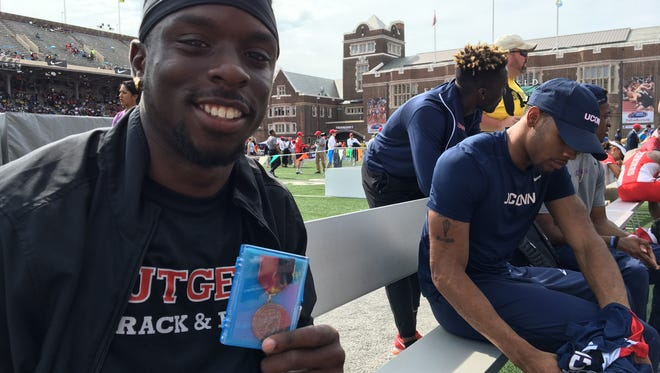 Rutgers postgrad Emeka Eze holds his silver medal at Franklin Field.