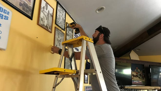 Thomas Bird carefully removes sports memorabilia from the walls of the former Jimmies Restaurant at Turtle Creek in Rockledge. Bird is opening a new sports bar in the location, but he plans to keep Jimmies' breakfast.