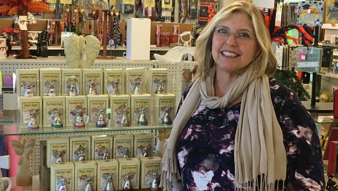 Lisa Peruchini, of Waynesboro, stands in front of her Everybody's Angel product line at Waynesboro Garden Center on March 11, 2017. Her angels have been licensed for worldwide distribution to stores. It was a happy surprise when she discovered them inside the garden center.