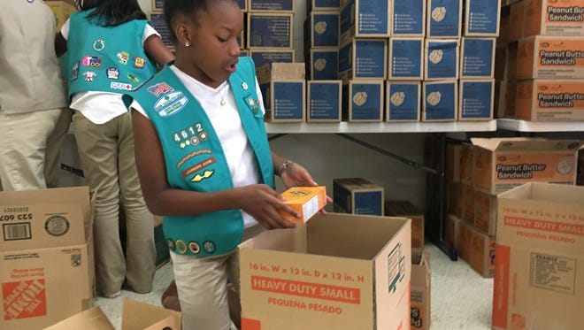 Girl Scout troop 4612 member Lailah Wideman, 10, packs Girl Scout cookies to send to troops currently serving overseas.