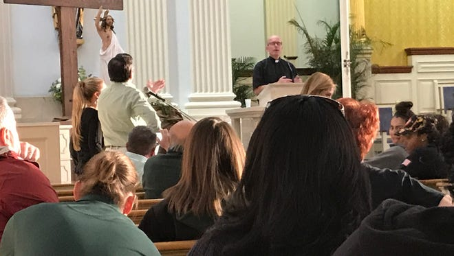 Fr. Mike Donovan, the pastor of Queen of Peace, is interrupted by a parent. A meeting was held at the church on May 10 about the closure of Queen of Peace High School.