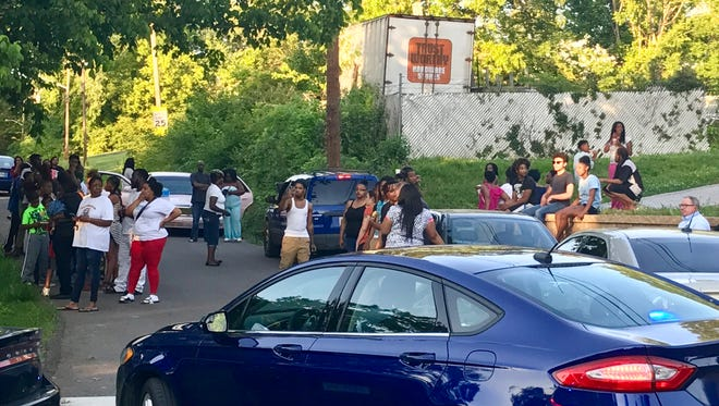 More than 50 people gathered at the intersection of Adair Avenue and Whittle Springs Road after a shooting killed two people at a North Knoxville home on Monday evening.