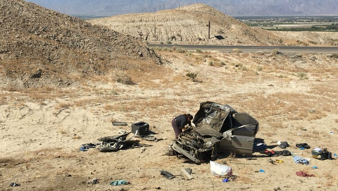 An official from the Riverside County Coroner's Office works after a crash on Interstate 10 near Coachella on Friday, May 19, 2017. A passenger was killed when the car veered off the highway and rolled. The driver was hospitalized.