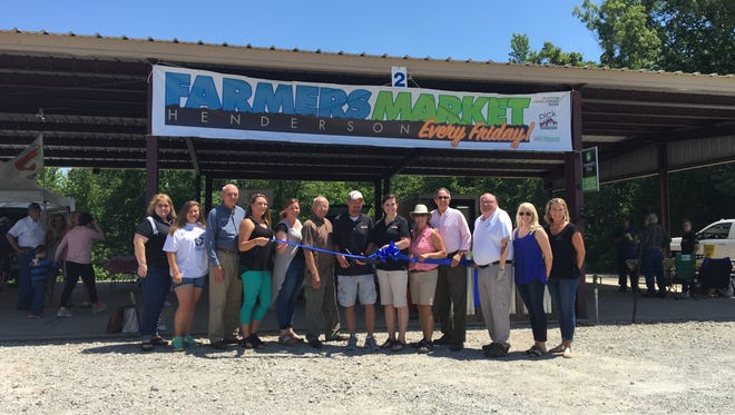 Steve Rickman cuts the ribbon at the Henderson Farmers Market on Friday, the first day the market was open.