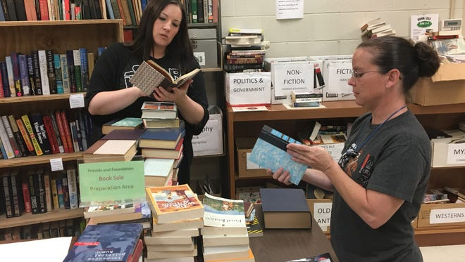 Jenci Spradlin, left, and Zoe Pride sort books for the Jackson-Madison County Library's annual book sale.